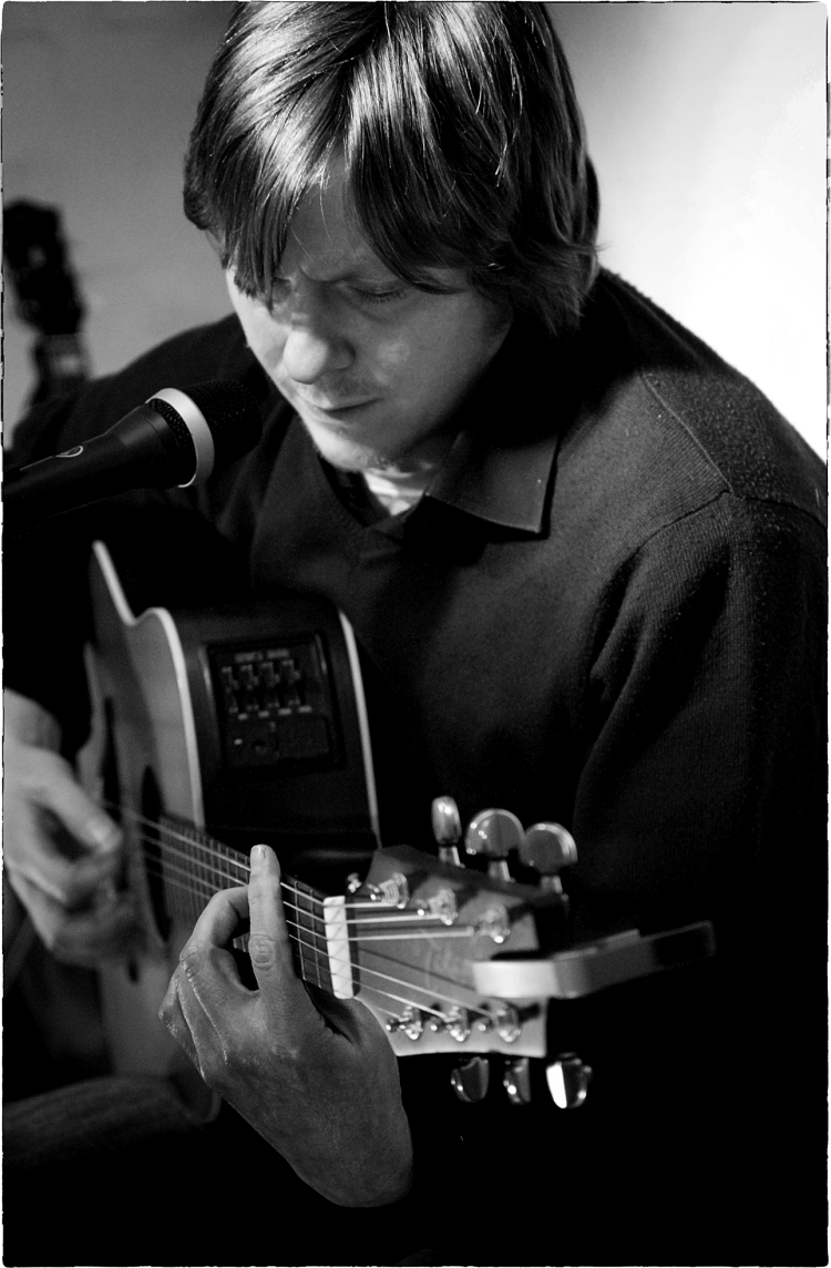 Sheffield based guitar lessons tutor Chris Murphy (playing an acoustic guitar)